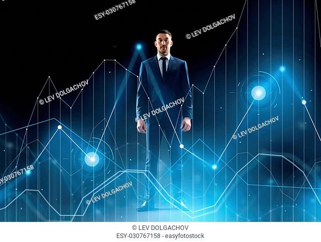 business, technology and people concept - businessman in suit with virtual chart over black background