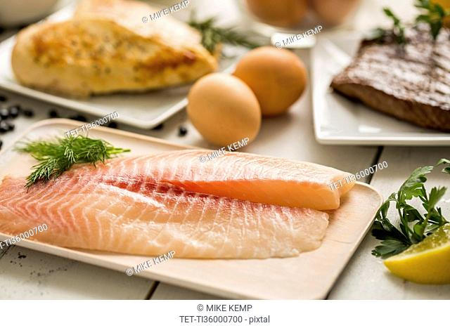 Raw tilapia fish on plate, chicken and eggs in background