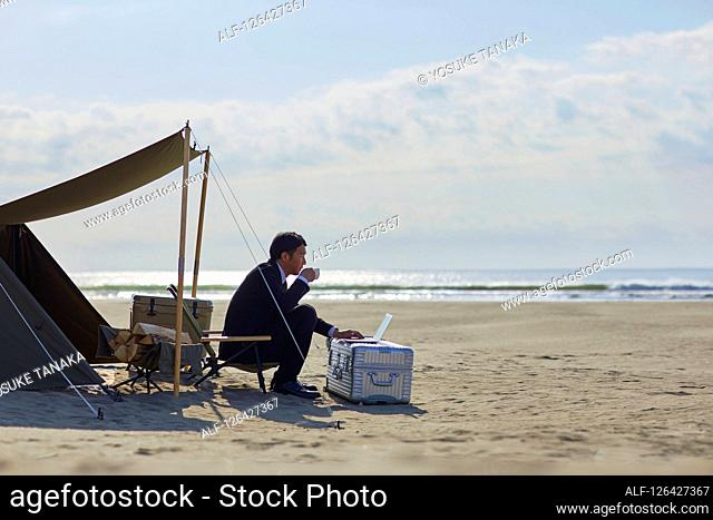 Japanese businessman working at the beach