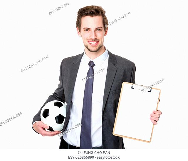 Man wearing business suit and holding soccer ball