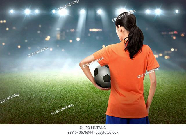 Young asian football player woman carrying the ball on the stadium