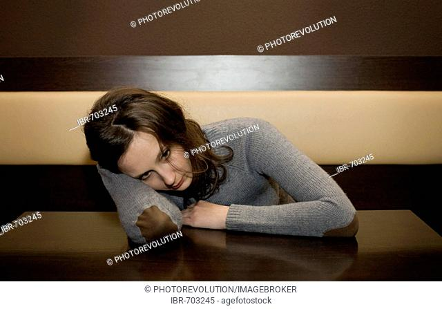Young woman leaned over the table at a bar, looking depressed