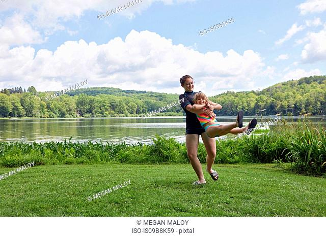 Girl swinging young girl around on grass, beside lake