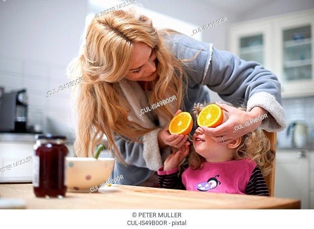 Young girl sitting at kitchen table, mother holding halved orange in front of daughter's eyes