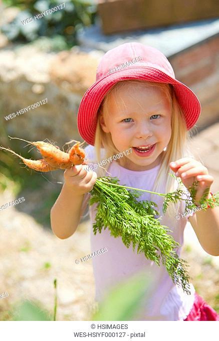 Germany, Bavaria, Girl picking carrots in garden