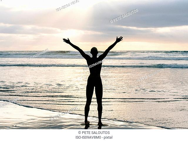 Silhouette of person raising arms on beach