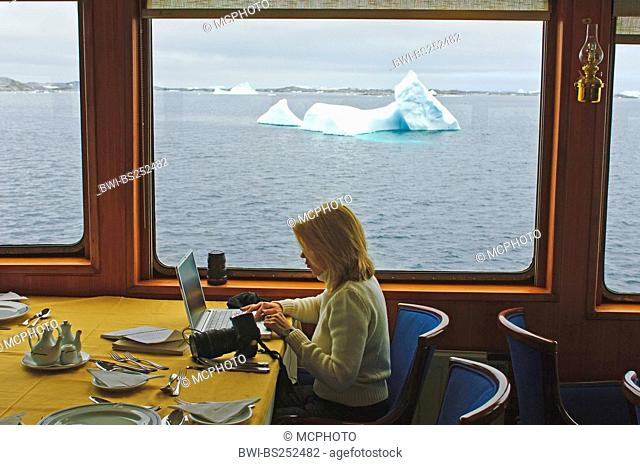 passenger with camera and laptop in front of window of a ship, icebergs in background, Antarctica