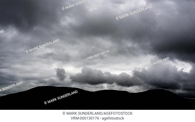 Time lapse of dark clouds moving over the silhouettes of Park Fell Simon Fell and the flat topped Ingleborough from Ribblehead in the Yorkshire Dales England