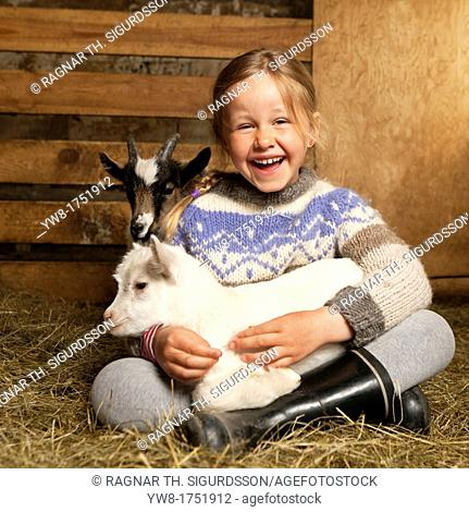 Girl holidng goat kid, Goat farm Iceland