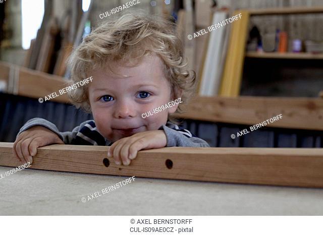 Close up portrait of male toddler inside boat in workshop