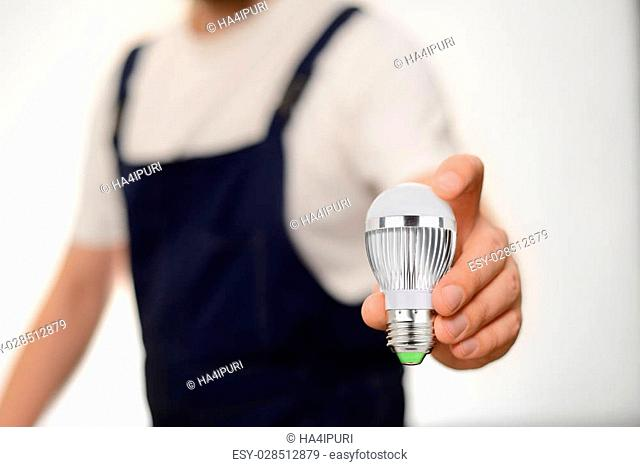 Worker in overall holding modern LED bulb in his hand over white background
