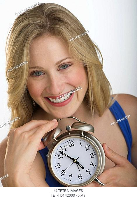 Happy blond woman holding an alarm clock