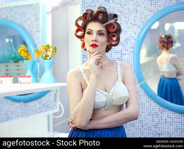 Portrait of vintage styled woman in a mid-century bathroom, with hair curlers in her hair