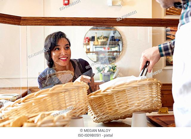 Customer in bakery pointing to baked goods, worker selecting it for her with tongs