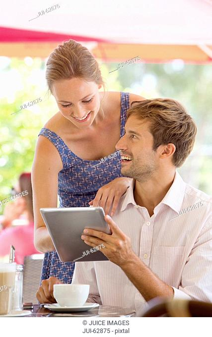 Couple looking at digital tablet in outdoor cafe