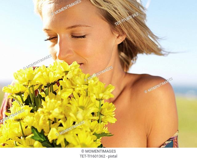 Blond woman smelling yellow flowers