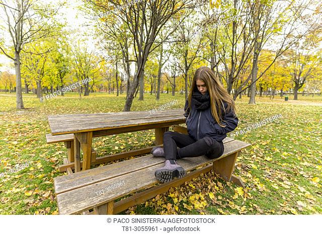 Thoughtful girl sitting along on park bench in the Prater, Vienna, Austria