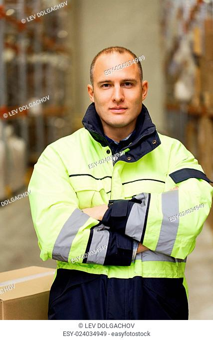 logistic, delivery, shipment, people and export concept - happy man or manual worker in coveralls with boxes at warehouse