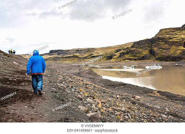 travel to Iceland - tourists hike on path from Solheimajokull glacier (South glacial tongue of Myrdalsjokull ice cap) in Katla Geopark on Icelandic Atlantic...