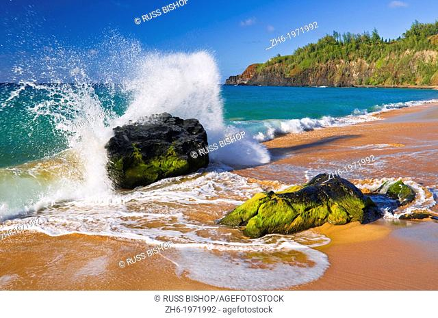 Surf crashing on rocks at Secret Beach (Kauapea Beach), Kilauea Lighthouse visible, Kauai, Hawaii USA
