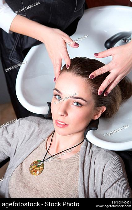 Hairdresser washing hair of beautiful lady in hairdressing saloon. Client having her hair wash by barber girl