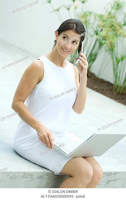 Woman sitting, using cell phone, holding laptop computer on lap