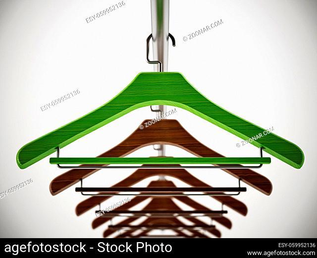 Green clothes-hanger stands out among regular hangers. 3D illustration