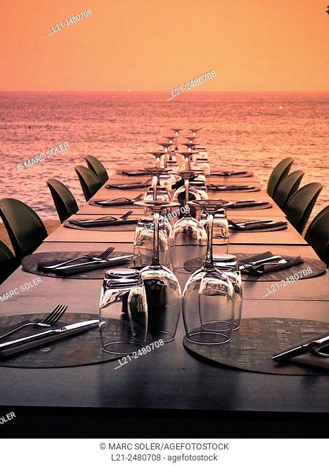 Table and chairs with cutlery and glasses near sea at sunset. Barcelona, Catalonia, Spain