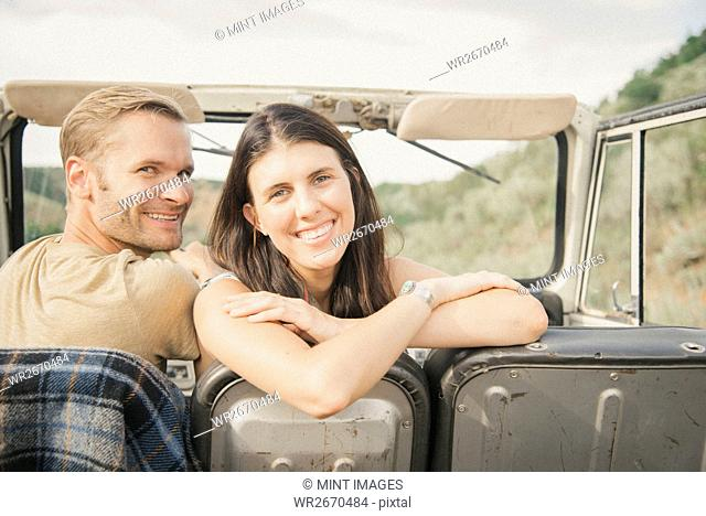 A couple on a road trip in a jeep side by side, a woman looking over her shoulder