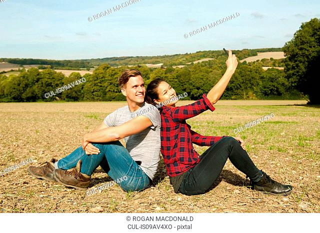 Young hiking couple sitting back to back in field taking smartphone selfie, Great Missenden, Buckinghamshire, U.K