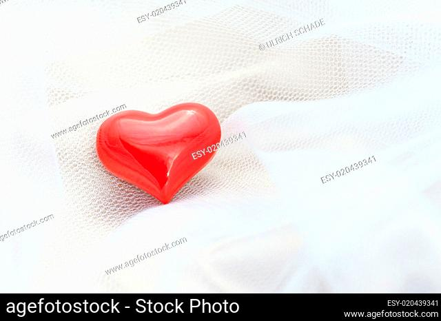 Red heart on a white veil