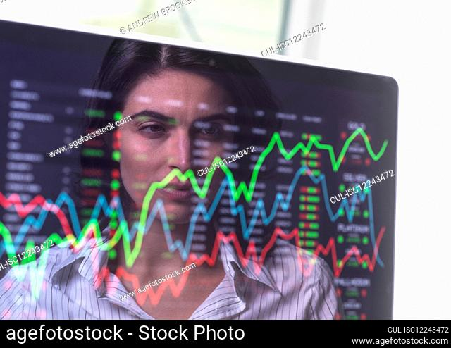 Female analyst viewing financial market data on a screen