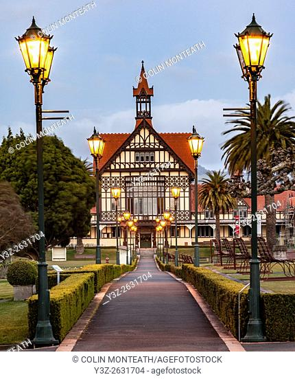 Rotorua Museum entrance pathway lined by lamps and Maori wooden carved figures, dusk, Government gardens, Rotorua