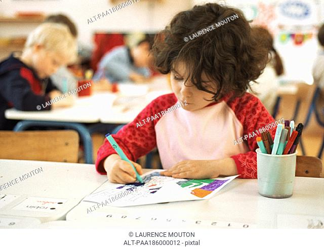 Child sitting at table, drawing, head and shoulders