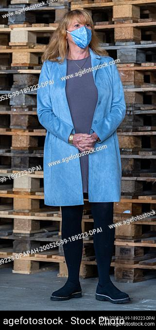 25 May 2020, Saxony, Dresden: Petra Köpping (SPD), Minister of Social Affairs of Saxony, is standing in a warehouse of the Tafel in front of a stack of pallets