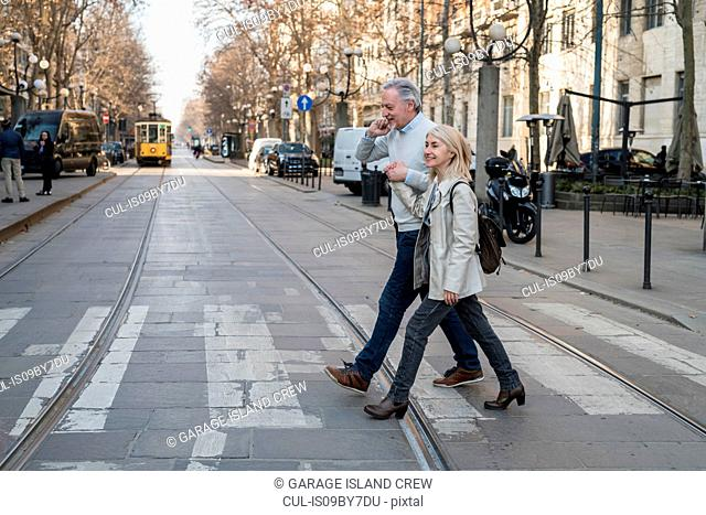 Senior couple crossing street in city
