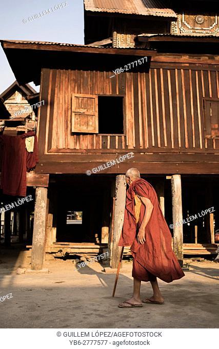 Old Buddhist monk walking by the Shwe Yan Pyay Monastery in Nyaungshwe, Myanmar