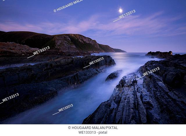 Landscape photo of a full moon rising over the sea near the Storms River Mouth. Tsitsikamma National Park, Western Cape, South Africa