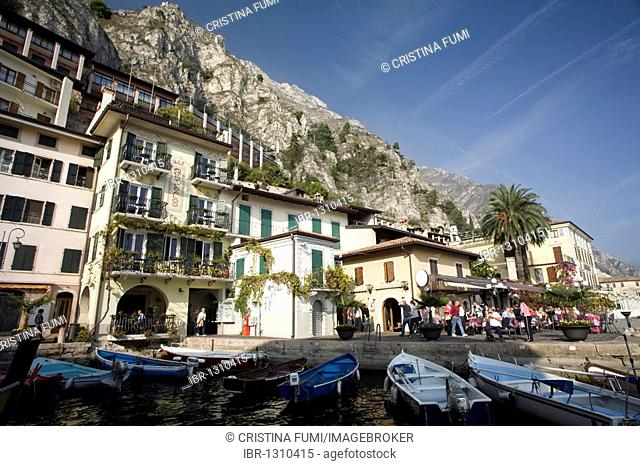 Limone sul Garda harbour on the lake with boats and touristic hotels and restaurants in the bay, Lake Garda, Italy, Europe