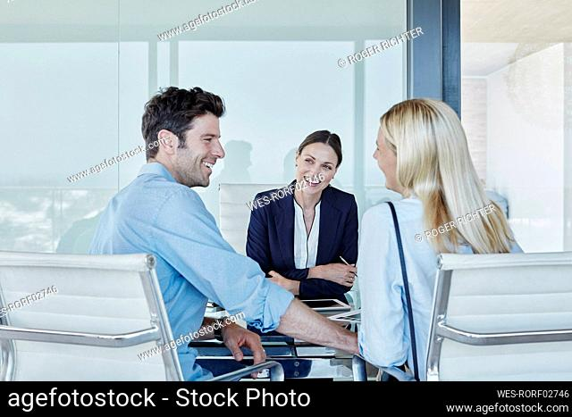 Smiling female real estate agent looking at cheerful couple sitting at table
