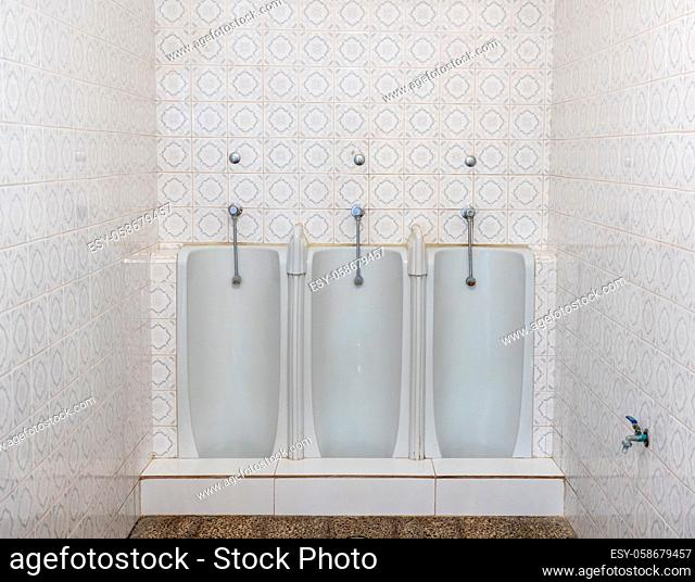 Set of three side by side full length mens urinals in porcelain against a tiled wall in small restroom