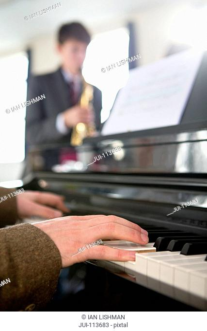 Music teacher playing piano with high school student playing saxophone in background