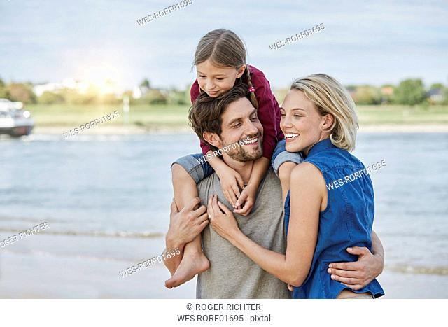 Germany, Duesseldorf, happy family with daughter at Rhine riverbank