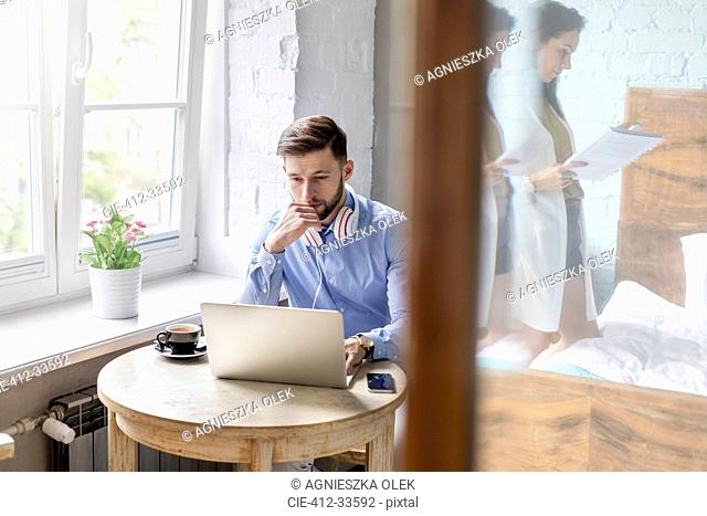 Man working at laptop in apartment