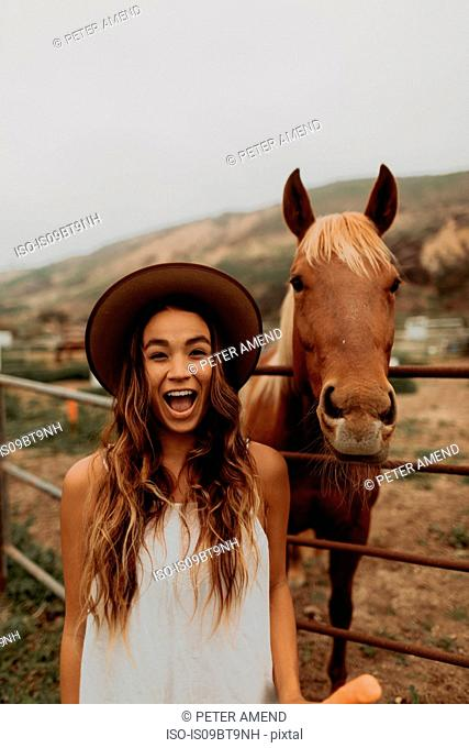 Young woman in felt hat next to horse, portrait, Jalama, California, USA
