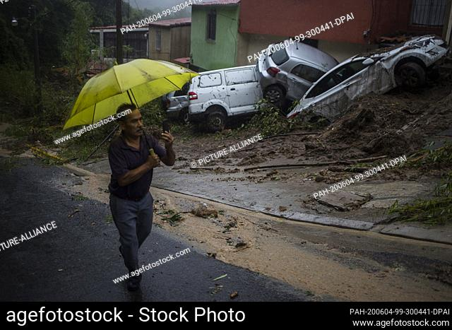 03 June 2020, El Salvador, Santo Tomás: In the municipality of Panchimalco, a man with an umbrella walks past houses in front of which vehicles have been pushed...