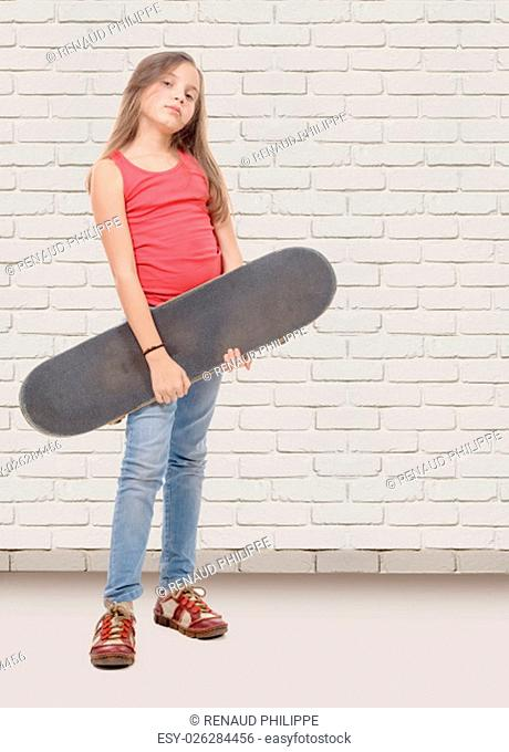 a pretty little girl with skateboard, white brick wall background