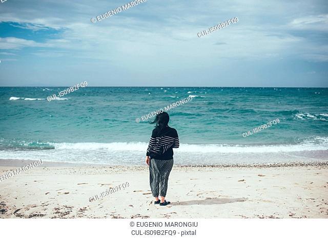Rear view of woman on beach looking at ocean, Sorso, Sassari, Italy