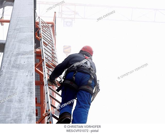 Germany, Bavaria, Garmisch-Partenkirchen, Zugspitze, installer climbing ladder on pole at goods cable lift