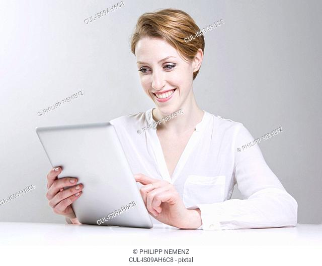 Portrait of young woman, using digital tablet